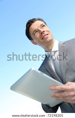 Portrait of businessman working on electronic tablet - stock photo