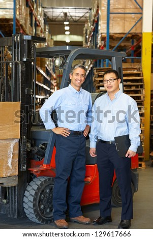 Portrait Of Businessmen With Fork Lift Truck In Warehouse - stock photo