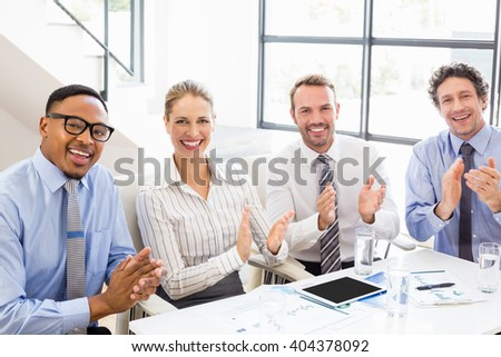 Portrait of businesspeople applauding while in a meeting at office - stock photo
