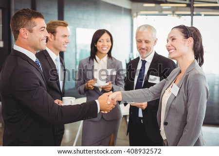 Portrait of businesspeople having tea and interacting during break time in office - stock photo