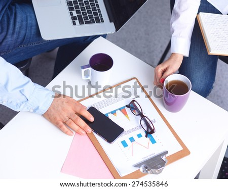 Portrait of  businesspeople sitting at  desk with a laptop - stock photo
