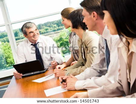Portrait of businesspeople sitting at the table and looking at boss - stock photo