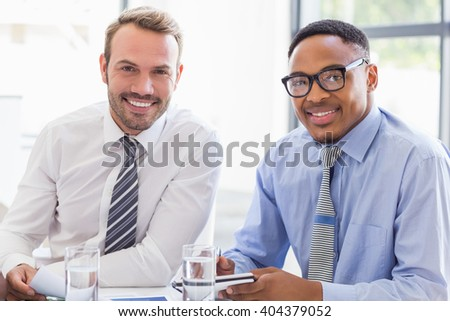 Portrait of businesspeople smiling in meeting at office - stock photo