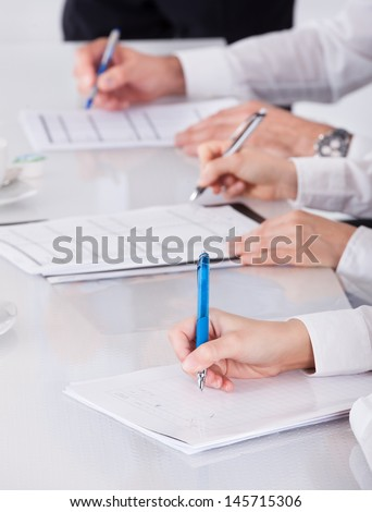 Portrait Of Businesspeople Writing Notes In Business Meeting