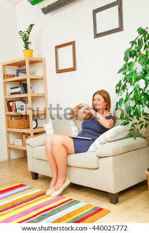 Portrait of businesswoman communicating with friends while working on laptop computer at home. Happy red haired lady showing heart with her hands. - stock photo