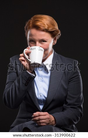 Portrait of businesswoman drinking coffee and looking at the camera. Lady in business suit posing in studio isolated on black background.