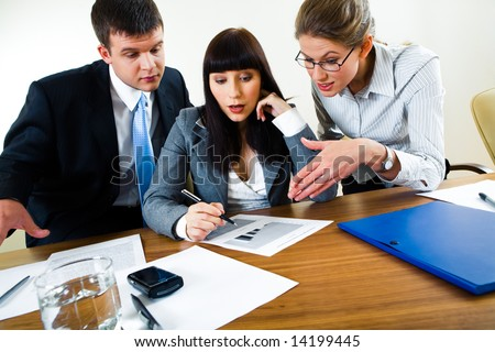 Portrait of businesswoman explaining business-plan to her coworkers - stock photo