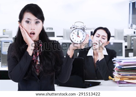 Portrait of businesswoman holding alarm clock and her friend looks yawning on the back. Shot in the office - stock photo