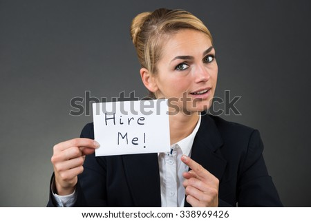 Portrait of businesswoman holding paper with hire me text over gray background