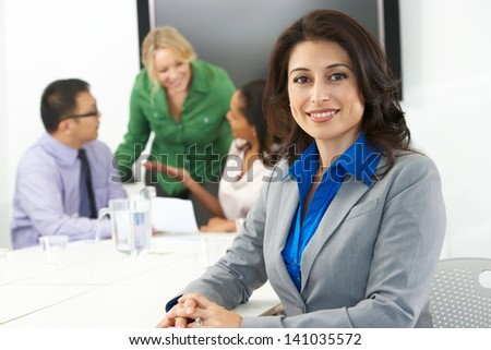 Portrait Of Businesswoman In Boardroom With Colleagues - stock photo