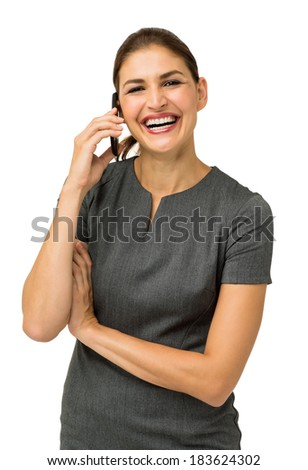 Portrait of businesswoman laughing while using smart phone against white background. Vertical shot. - stock photo