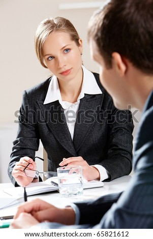Portrait of businesswoman listening to her colleague attentively - stock photo