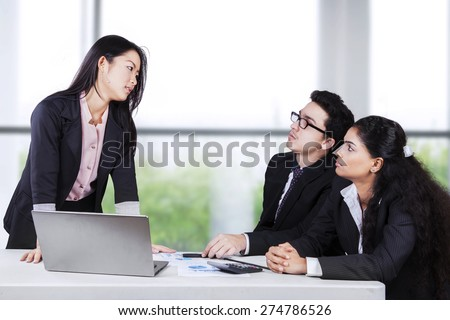 Portrait of businesswoman looking at her employees seriously with angry expression - stock photo