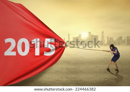 Portrait of businesswoman pulling a banner with number 2015 in the morning - stock photo