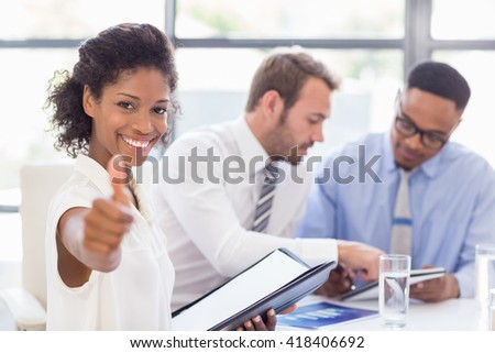 Portrait of businesswoman showing her thumbs up in office while colleagues discussing in background - stock photo