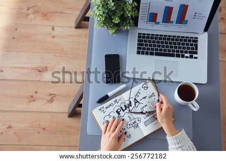 Portrait of  businesswoman sitting at  desk with a laptop - stock photo