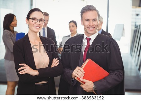 Portrait of businesswoman standing with lawyer in office - stock photo