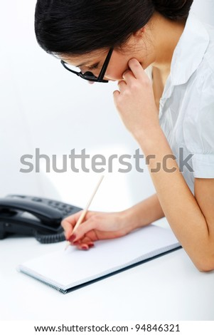 Portrait of  businesswoman taking note in a notepad at office