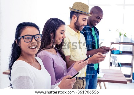 Portrait of businesswoman using phone with colleagues in creative office - stock photo