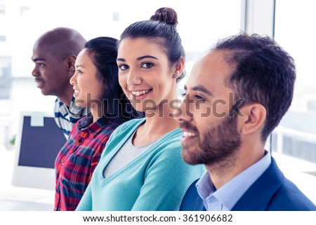 Portrait of businesswoman with colleagues standing in creative office