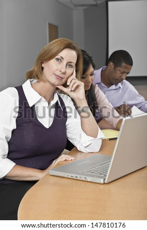 Portrait of businesswoman with laptop and multiethnic colleagues in conference room - stock photo