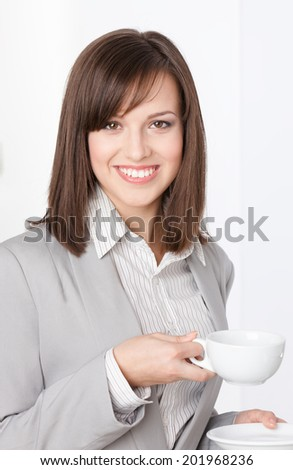 Portrait of businesswoman with white cup and saucer, isolated on white - stock photo