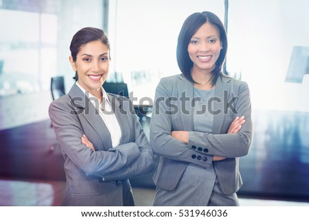 Portrait of businesswomen standing with arms crossed in office
