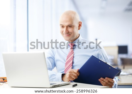 Portrait of busy broker sitting at stock exchange in front of computer while holding file in his hand. Businessman working at office. - stock photo