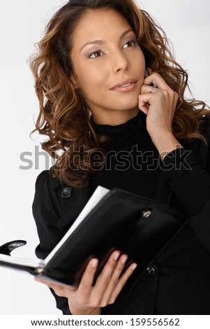 Portrait of busy businesswoman, talking on mobile, holding personal organizer, looking away.