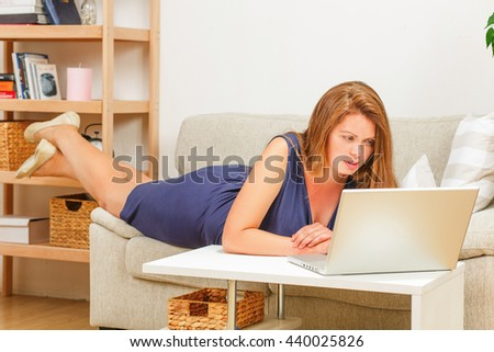 Portrait of busy businesswoman working on laptop computer at home. Beautiful lady looking at screen while lying on sofa or couch.