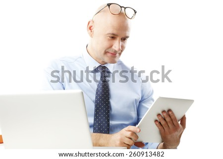 Portrait of busy financial advisor working at digital tablet while sitting at desk. Isolated on white background. - stock photo