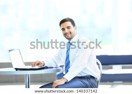 Portrait of busy manager typing on the laptop in the office - stock photo