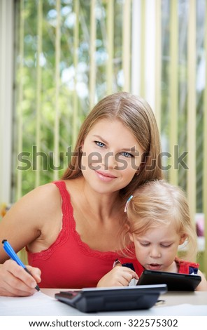 Portrait of busy mother working from home sitting at the desk with her little daughter. Young attractive woman with cute blond girl calculating family budget.  - stock photo