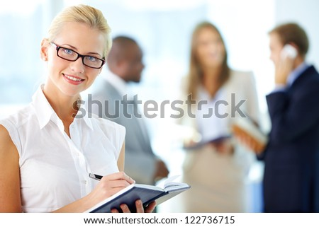Portrait of busy secretary looking at camera