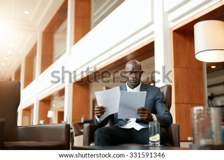 Portrait of busy young businessman sitting at hotel lobby going through documents. African business executive reading contract papers. - stock photo