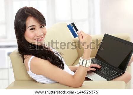 portrait of busy young woman sitting in sofa using a laptop and hold the credit card