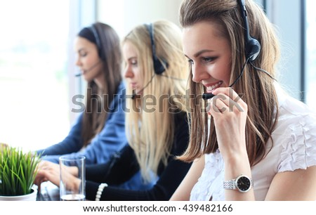 Portrait of call center worker accompanied by her team. Smiling customer support operator at work. - stock photo