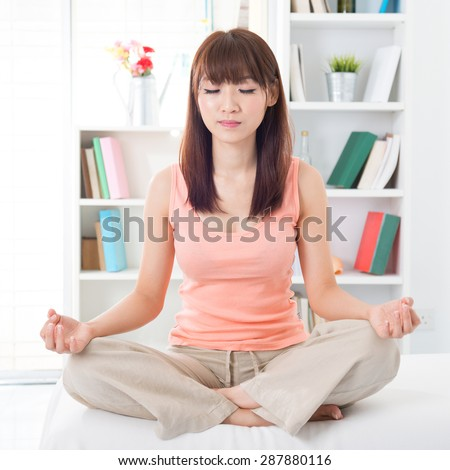 Portrait of calm Asian girl meditating in the morning. Young woman indoors living lifestyle at home.