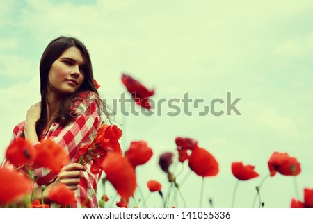 Portrait of calm beautiful girl through a poppy field, summer outdoor. Toned, noise added. - stock photo