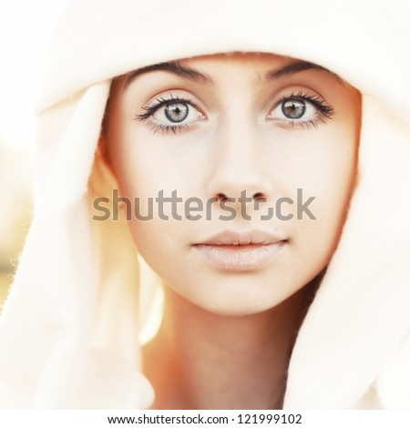 Portrait of calm beautiful young woman in head scarf close up against bright sunlight - stock photo