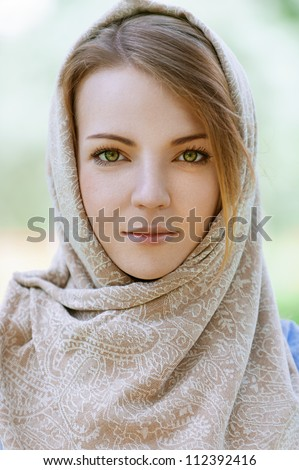 Portrait of calm beautiful young woman in head scarf close up, against green of summer park. - stock photo
