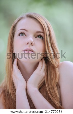 Portrait of calm beautiful young woman with bare shoulders, against green of summer park. - stock photo