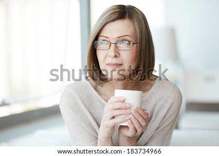Portrait of calm mature woman with cup - stock photo