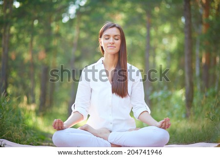 Portrait of calm woman sitting in pose of lotus in natural environment - stock photo