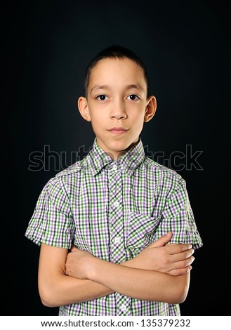portrait of calm young boy looking at camera over black background