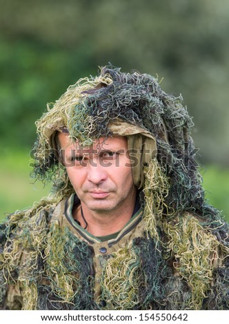 Portrait of camouflaged man in forest - stock photo