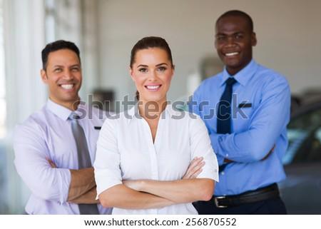 portrait of car dealership staff standing in showroom - stock photo