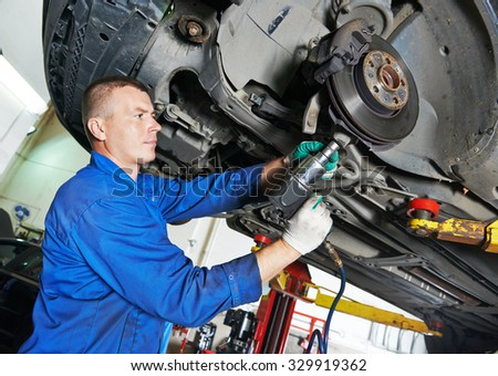 portrait of car mechanic worker before repairing suspension of lifted automobile at auto repair garage shop station - stock photo