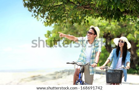 Portrait of carefree couple having fun and smiling riding bicycle at the beach - stock photo