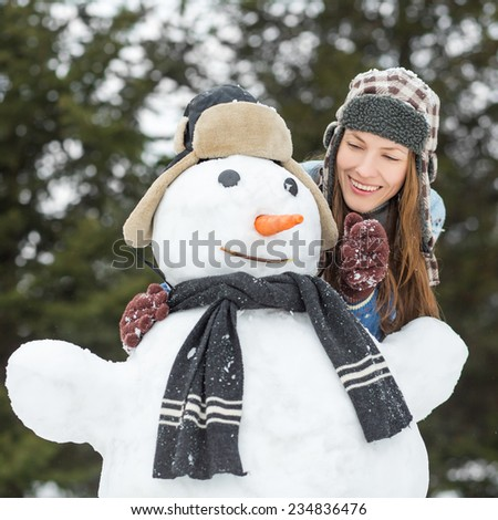 Portrait of carefree winter woman with snowman, trying to take carrot from snowman. focus on woman - stock photo